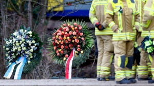 Rescue workers stand besides wreaths in front of two trains that collided head-on near Bad Aibling, Germany, Wednesday, Feb. 10, 2016. (AP Photo/Matthias Schrader)