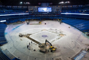Construction workers hammer out concrete as they install the new dirt infield for the Toronto Blue Jays upcoming season at the Rogers Centre in Toronto on Wednesday, Feb. 10, 2016. (The Canadian Press/Nathan Denette)