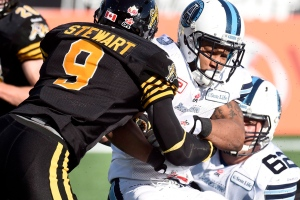 Toronto Argonauts' Brandon Whitaker (3) makes a touchdown as Hamilton Tiger-Cats' Brandon Stewart (9) grabs at the ball during first half CFL Eastern Division Semifinal football action, in Hamilton, Ont., on Sunday, Nov. 15, 2015. (The Canadian Press/Frank Gunn)