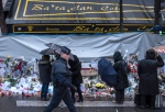 In this Nov. 25, 2015 file photo, a policeman walks as people pay respects to victims of the Paris attacks in front of the Bataclan concert hall, in Paris. (AP Photo/Kamil Zihnioglu)
