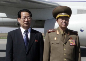 In this May 22, 2013 file photo, Kim Hyong Jun, deputy minister Foreign Affairs, and Ri Yong Gil, col. gen. of the Korean People's Army, pose before leaving the Pyongyang Airport in North Korea for China. (AP Photo/Kim Kwang Hyon)