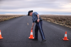 In a Jan. 28, 2016 file photo, an officer with the Oregon State Police moves a cone to establish a roadblock along one of the routes to the Malheur National Wildlife Refuge in Harney County, Ore. The FBI said Wednesday, Feb. 10, 2016, that it has moved to contain the last few occupiers of an Oregon wildlife refuge who were part of a protest that began more than a month ago over federal land policy. (Beth Nakamura/The Oregonian via AP, File)