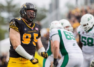 Hamilton Tiger-Cats defensive tackle Brian Bulcke, left, celebrates his sack on Saskatchewan Roughriders quarterback Tino Sunseri during the first half of their CFL game in Hamilton, Ont., Sunday, Sept. 14, 2014. (The Canadian Press/Aaron Lynett)