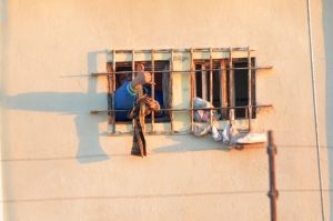 An inmate shouts and makes a hand sign from behind his barred window at the Topo Chico prison, after a riot broke out around midnight in Monterrey, Mexico, Thursday, Feb. 11, 2016. (AP Photo/Emilio Vazquez)