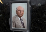 This July 28, 2014, photo shows Jakob Denzinger's portrait on the tombstone of his empty grave in Cepin, eastern Croatia. The suspected former Nazi prison guard at Auschwitz and other death camps, Jakob Denzinger, has died in his native Croatia at the age of 92. (AP Photo/Darko Bandic)