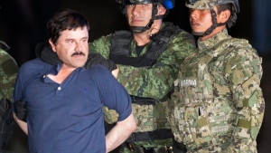 Joaquin 'El Chapo' Guzman is made to face the press as he is escorted to a helicopter in handcuffs by Mexican soldiers and marines at a federal hangar in Mexico City, Mexico, following his recapture six months after escaping from a maximum security prison on Jan. 8, 2016. (AP / Eduardo Verdugo)
