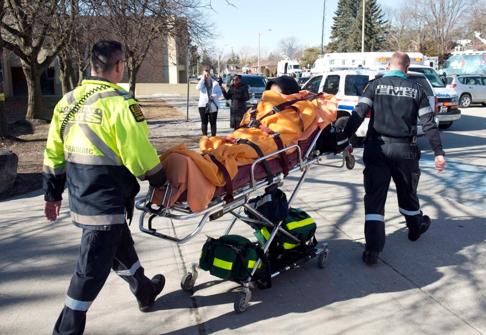 A victim is taken away on a stretcher following a stabbing incident at Dunbarton High School in Pickering, Ont., on Tuesday, Feb. 23, 2016. High-school students described a chaotic scene at a suburban Toronto high school on Tuesday after a female classmate ran down the hallways knifing people, leaving six students and two teachers with non-serious injuries. THE CANADIAN PRESS/Salvatore Sacco