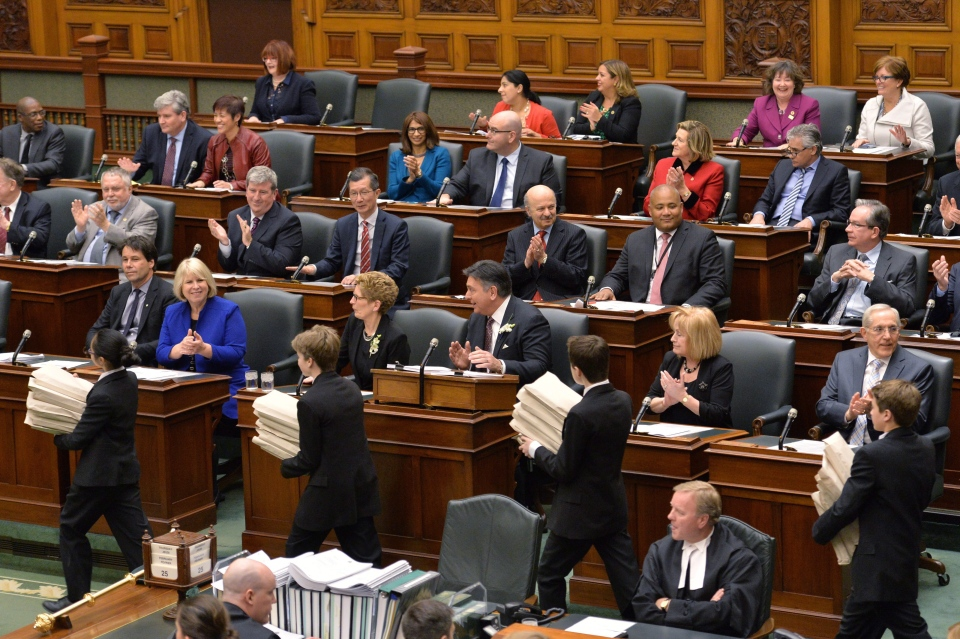 Pages deliver the Ontario 2016 budget to MPPs at Queen's Park in Toronto on Thursday, February 25, 2016. Ontario Finance Minister Charles Sousa is at centre right and Premier Kathleen Wynne is at centre left. THE CANADIAN PRESS/Nathan Denette