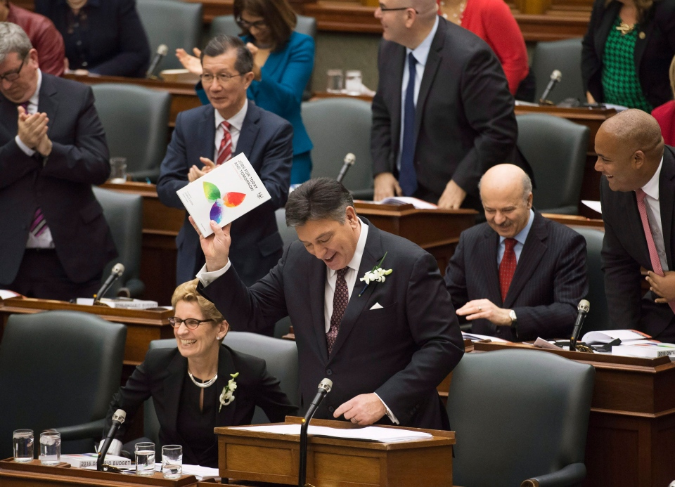 Ontario Finance Minister Charles Sousa, right, delivers the Ontario 2016 budget next to Premier Kathleen Wynne, left, at Queen's Park in Toronto on Thursday, February 25, 2016. THE CANADIAN PRESS/Nathan Denette