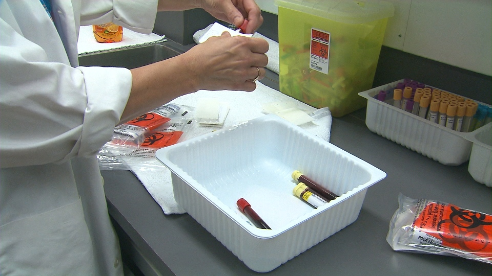 A worker at a medical laboratory collects samples for testing in this file photo.