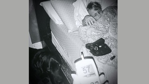 Luke, 7, sleeps as his diabetic alert dog, 'Jedi', looks on. (Facebook)