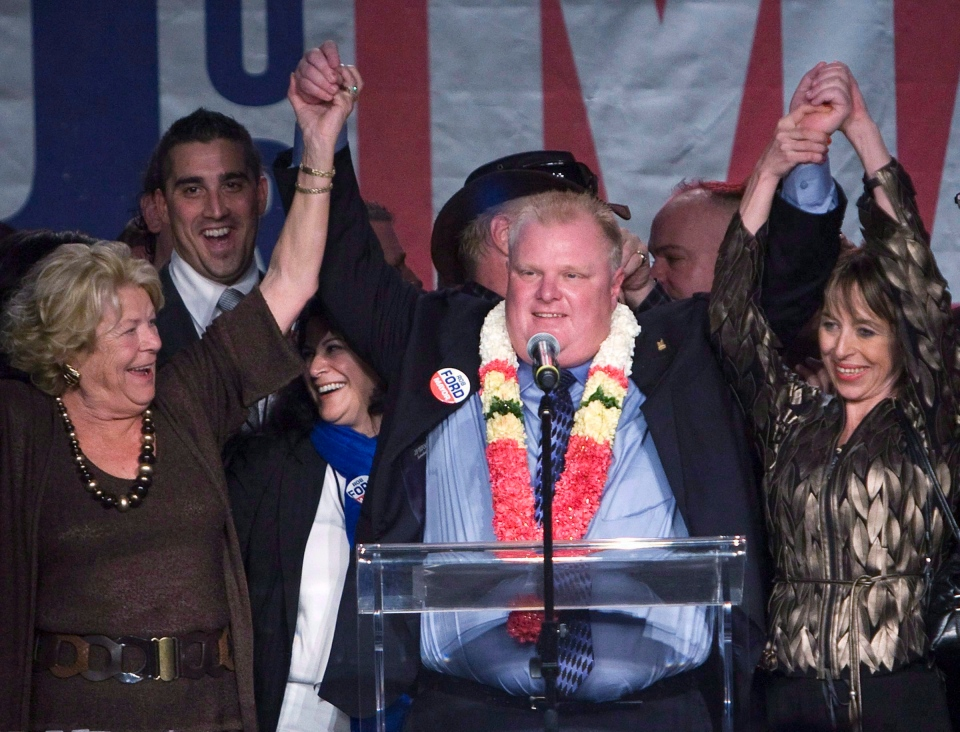 Rob Ford, centre, raises his arms with his wife Renata, right, and mother Diane, left, as he speaks to supporters in Toronto on October 25, 2010. Former Toronto Mayor Rob Ford, whose scandal-plagued time in office made him an international celebrity, has died. THE CANADIAN PRESS/Nathan Denette