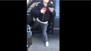 A woman prepares to hurl a Tim Hortons beverage at a man filming her for using an accessible parking spot. (YouTube)