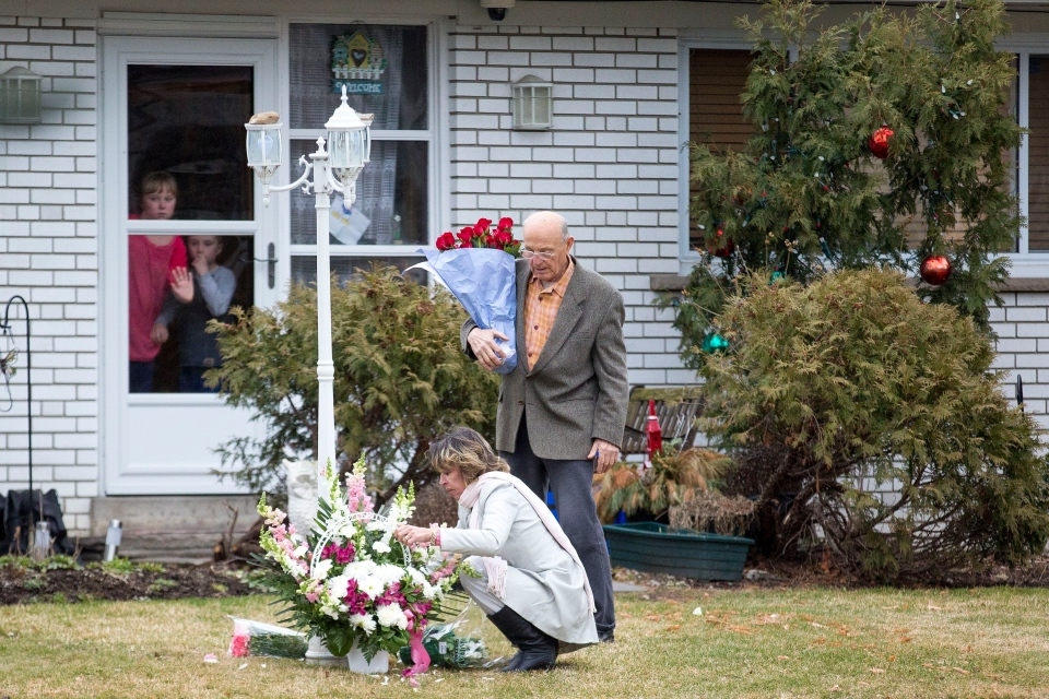 Stephanie and Doug Ford watch as their mother Renata arranges flowers left at the family home in Etobicoke following the death of Coun. Rob Ford on Tuesday, March 22, 2016. Neighbour Zdravko Gagro looks on. (The Toronto Star/Carlos Osorio)