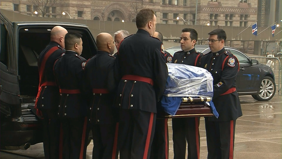 A ceremonial guard carries Rob Ford's casket into city hall ahead of a public visitation on March 28, 2016.