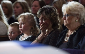 Former Toronto mayor Rob Ford's widow Renata cries next to her husband's casket at St. James Cathedral in Toronto on Wednesday, March 30, 2016. Their children Stephanie and Dougie are at left and Rob Ford's mother Diane is at right. Ford died of cancer last week at the age of 46. THE CANADIAN PRESS/Nathan Denette