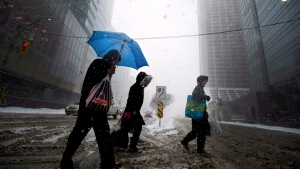 A man uses an umbrella to take cover from the blizzard like conditions in Toronto on Wednesday, March 12, 2014. THE CANADIAN PRESS/Nathan Denette