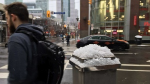 A man crosses John Street in downtown Toronto as snow begins to fall Sunday April 3, 2016. (Joshua Freeman /CP24)