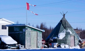 A tattered Canadian flag flies over a building in Attawapiskat, Ont., on November 29, 2011. A remote northern Ontario First Nation has declared a state of emergency after numerous suicide attempts this week. THE CANADIAN PRESS/Adrian Wyld