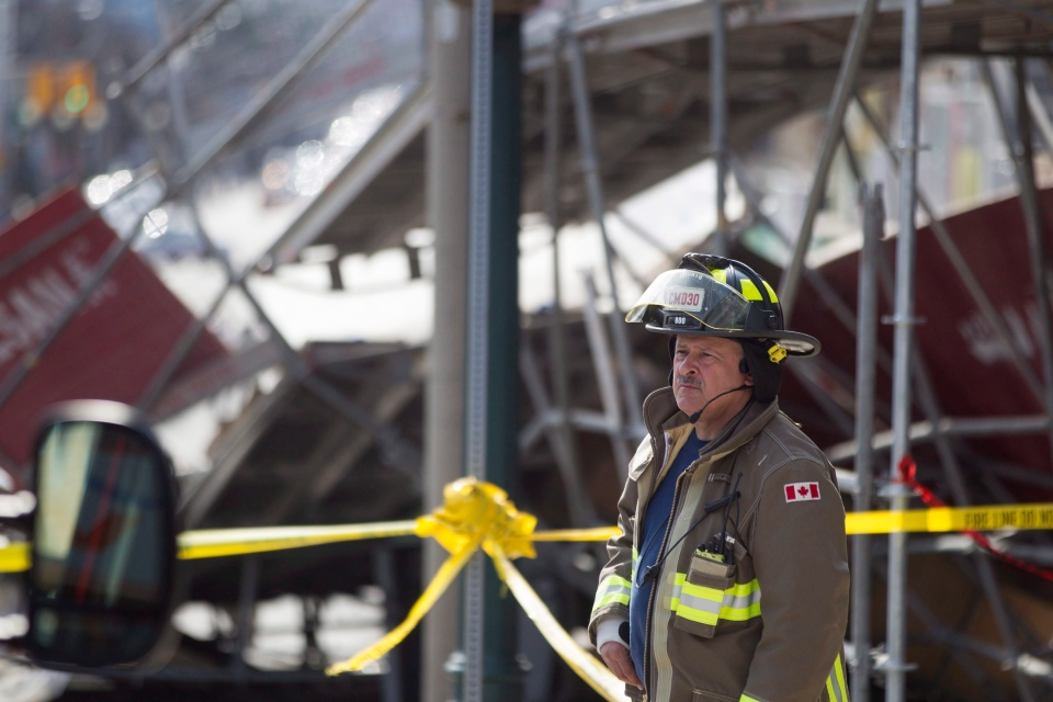 A member of the fire department stands in front of wreckage after part of a building and its scaffolding collapsed on a construction site in Toronto on Monday, April 18, 2016. (The Canadian Press/Chris Young)