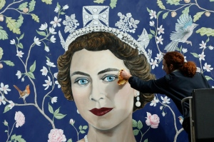Workmen install a new mural by Frederick Wimsett, of Britain's Queen Elizabeth II to mark her 90th birthday celebrations, in central London, Tuesday, April, 19, 2016. The longest-reigning monarch in British history turns 90 on Thursday. (AP Photo/Alastair Grant)