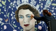 Workmen install a new mural by Frederick Wimsett, of Britain's Queen Elizabeth II to mark her 90th birthday celebrations, in central London, Tuesday, April, 19, 2016.  (AP Photo/Alastair Grant)