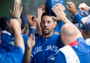 Toronto Blue Jays Chris Colabello is congratulated by teammates after scoring on the Philadelphia Phillies in the first inning of Spring Training action in Clearwater, Fla. on Tuesday, March 1, 2016. (The Canadian Press/Frank Gunn)