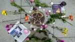 Flower are placed over musician Prince's star on a makeshift memorial on the sidewalk outside of the Warner Theatre in Washington, Friday, April 22, 2016. The pop star died Thursday at age 57. ( AP Photo/Jose Luis Magana)