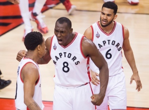 Toronto Raptors centre Bismack Biyombo (8) and Raptors guard Cory Joseph (6) react after Toronto Raptors guard DeMar DeRozan (10) slam dunked the ball against the Indiana Pacers during first half round one NBA basketball playoff action in Toronto on Tuesday, April 26, 2016. THE CANADIAN PRESS/Nathan Denette