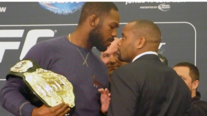 UFC light-heavyweight champion Jon (Bones) Jones, left, and challenger Daniel (DC) Cormier get up-close and personal during a staredown in advance of UFC 182, prompting UFC president Dana White to put his arm between the two during a media event in Las Vegas on Thursday, Jan. 1, 2015. THE CANADIAN PRESS/Neil Davidson