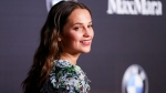 In this Feb. 26, 2016 file photo, Alicia Vikander arrives at the 9th Annual Women in Film Pre-Oscar Cocktail Party at Hyde Sunset Kitchen + Cocktails in Los Angeles. Vikander is following in Angelina Jolie's butt-kicking footsteps. The Swedish actress has signed on to play the role of Lara Croft in a new Tomb Raider movie from Norwegian director Roar Uthaug. MGM, Warner Bros. and GK Films announced the news Thursday, April 28, 2016. (Photo by Rich Fury/Invision/AP, File)