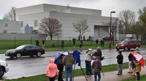 In this April 21, 2016 file photo, people stand outside entertainer Prince's Paisley Park compound in Chanhassen, Minn. Since Prince died, YouTube and other uploading sites have been flooded with hundreds of hours of the superstar musician's songs, concert footage, TV appearances and music videos. It's a sign that the notoriously tight copyright controls the artist maintained over his material is rapidly loosening, and raising hope that hardcore fans might someday hear the Holy Grail of Prince's music: unreleased recordings from the vault at Paisley Park. (Jim Gehrz/Star Tribune via AP, File)