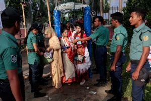 Bangladeshi policemen check people as they arrive to take part in a procession to celebrate Bengali New Year, in Dhaka, Bangladesh, Thursday, April 14, 2016. (AP Photo/A.M. Ahad)