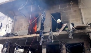 In this image made from video and posted online from Validated UGC, a firefighter tries to extinguish a building caught on fire after airstrikes hit Aleppo, Syria, Thursday, April 28, 2016. (Validated UGC via AP video)