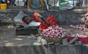 An Indian vendor selling onions on a sidewalk rests under the shade of a tree on a hot summer day in Hyderabad, India, Wednesday, April 20, 2016. (AP Photo/Mahesh Kumar A.)