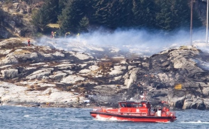 A search and rescue vessel patrols off the island of Turoey, near Bergen, Norway, as emergency workers attend the scene of a helicopter crash believed to have 13 people aboard, Friday April 29, 2016. The helicopter carrying around 13 people from an offshore oil field crashed Friday near the western Norwegian city of Bergen, police said. Many are feared dead. (Rune Nielsen / NTB scanpix via AP)