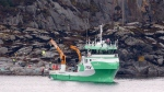 A recovery vessel lifts up parts of a crashed helicopter from off the island of Turoey, near Bergen, Norway, as emergency workers on the shoreline attend the scene Friday, April 29, 2016. The helicopter carrying around 13 people from an offshore oil field crashed Friday near the western Norwegian city of Bergen, police said. All aboard the helicopter were killed. (Vidar Ruud/NTB scanpix via AP)
