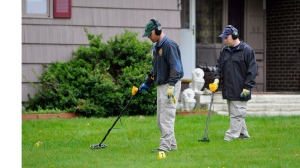 FILE - In this Thursday, May 10, 2012, file photo, law enforcement agents search the yard at the home of reputed Connecticut mobster Robert Gentile in Manchester, Conn. (AP Photo/Jessica Hill, File)