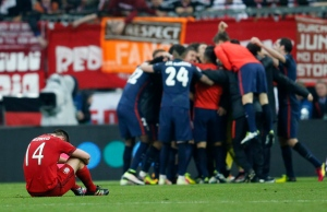 Bayern's Xabi Alonso sits on the pitch as Atletico players celebrate after advancing to the final after the final whistle of the Champions League second leg semifinal soccer match between Bayern Munich and Atletico de Madrid in Munich, Germany, Tuesday, May 3, 2016. (AP Photo/Michael Probst)