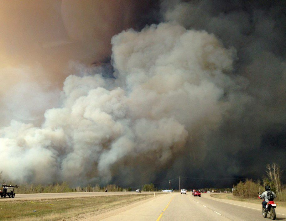 Smoke fills the air as people drive on a road in Fort McMurray, Alberta on Tuesday May 3, 2016 in this image provide by radio station CAOS91.1. (The Canadian Press/HO-CAOS91.1(KAOS))