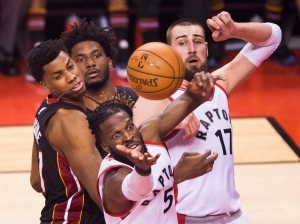 Toronto Raptors forward DeMarre Carroll (5) battles for the ball against Miami Heat centre Hassan Whiteside (21) and Heat forward Justise Winslow (20) as Raptors centre Jonas Valanciunas (17) looks on during first half second round NBA basketball playoff action in Toronto on Tuesday, May 3, 2016. (The Canadian Press/Nathan Denette)