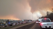 Smoke fills the air as cars line up on a road in Fort McMurray, Alberta on Tuesday May 3, 2016.  THE CANADIAN PRESS/Greg Halinda