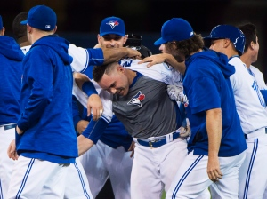 Toronto Blue Jays catcher Russell Martin, centre, is mobbed by teammates after hitting the game winning RBI single during ninth inning AL baseball action against the Texas Rangers in Toronto on Wednesday, May 4, 2016. (The Canadian Press/Nathan Denette)