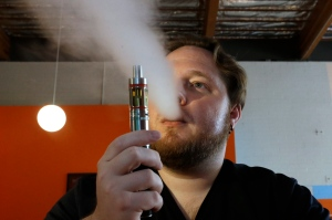 In this July 16, 2015 file photo, Bruce Schillin exhales from an e-cigarette at the Vapor Spot, in Sacramento, Calif. (AP Photo/Rich Pedroncelli, File)