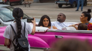 A woman uses her cellphone to take a picture American reality-show star Kim Kardashian West, center, and her husband Kanye West as they ride on a classic car along the streets of Havana, Cuba, Wednesday, May 4, 2016. Rap superstar Kanye West, his wife Kim Kardashian and members of her reality-show-star family have become the latest celebrities to visit Havana. They visited Havana's Museum of Rum Wednesday, stepping out of a hot-pink antique American convertible as they snapped selfies and were recorded by a television crew following them around. At right is Kourtney Mary Kardashian, (AP Photo/Desmond Boylan)