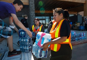 Volunteers load water for evacuees from the Fort McMurray wildfires at the evacuation centre in Lac la Biche, Alta., Friday, May 6, 2016. THE CANADIAN PRESS/Jeff McIntosh