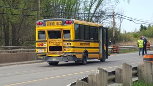 Emergency workers are shown alongside a school bus that was rear-ended by a transport truck in Halton Region on Thursday morning. (Dave Ritchie)