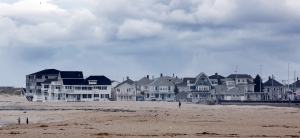 People walk near ocean front property in New Hampshire's summer resort area of Hampton Beach Tuesday, May 3, 2016, in Hampton, N.H. Worries over lost tax revenue have state and local officials grappling with how to regulate private rentals through online platforms such as Airbnb. Lawmakers are starting with efforts to ensure operators are paying taxes, but some city officials want more say over how and where short-term rentals can operate. (AP Photo/Jim Cole)