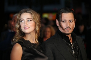 """FILE - In this Oct. 11, 2015 file photo, Amber Heard, left, and Johnny Depp arrive at the premiere of Depp's film """"Black Mass,"""" at the London film festival. Court records show Heard filed for divorce in Los Angeles Superior Court on Monday, May 23, 2016, citing irreconcilable differences. The pair were married in February 2015 and have no children together. (Photo by Joel Ryan/Invision/AP, File)"""