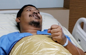 In this image made from video, Attaporn Boonmakchuay gestures while talking to reporters while lying in a hospital bed following a snake attack at his home in Chachoengsao, 90 km east of the capital Bangkok, on Wednesday, May 25, 2016. (BBTV CH7 Thailand via AP)